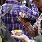Tourist taking a photo of the egg tart at Tai Cheong Bakery in Hong Kong. Photo by alphacityguides.
