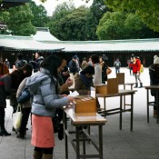 Locals writing prayers on Ema tables at Meiji Shrine in Tokyo. Photo by alphacityguides.