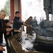 Family drinking from the holy water fountain at Sensoji Temple in Tokyo. Photo by alphacityguides.